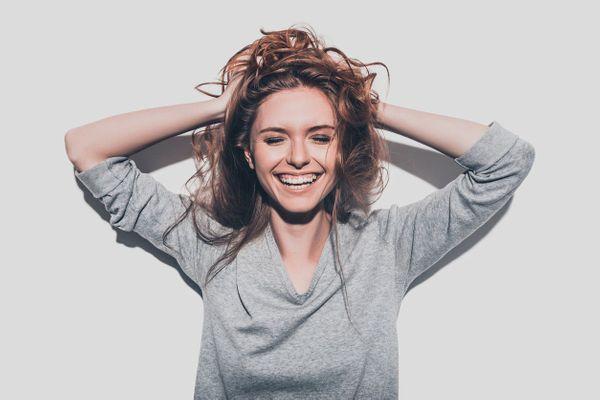 femme qui se tient la tête avec les mains et souris